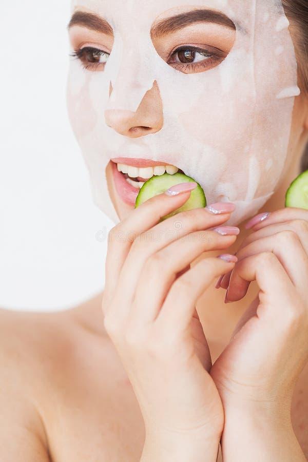 应用关心皮肤透明油漆 有板料面具的美丽的女孩在她的面孔 免版税图库摄影