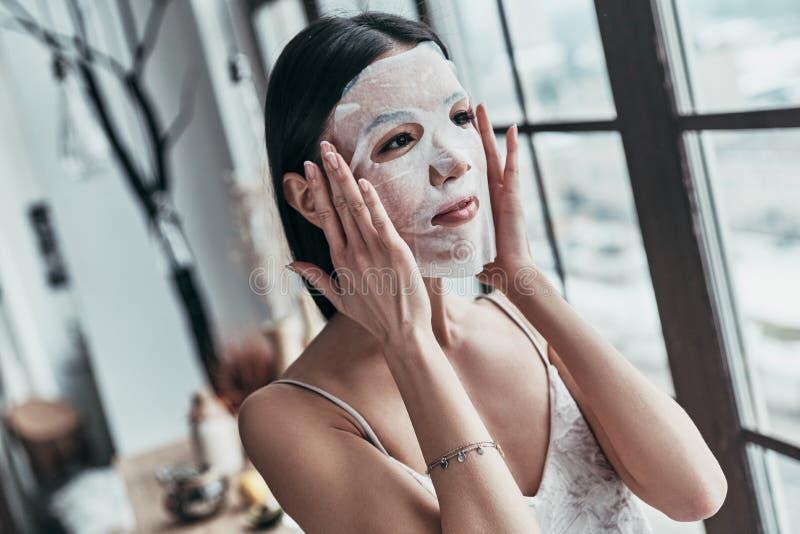 应用关心皮肤透明油漆 申请面部面具和looki的可爱的少妇 图库摄影