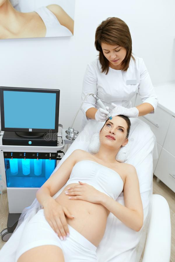 应用关心皮肤透明油漆 面孔的孕妇洗涤在秀丽诊所的 库存照片