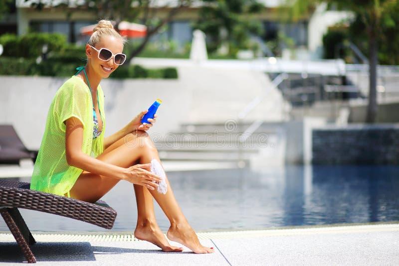 应用化妆水保护晒黑妇女 免版税库存图片