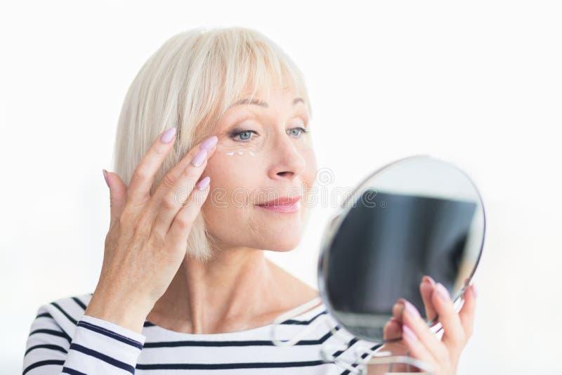 应用反皱痕奶油的美丽的年长妇女,拿着镜子 免版税图库摄影