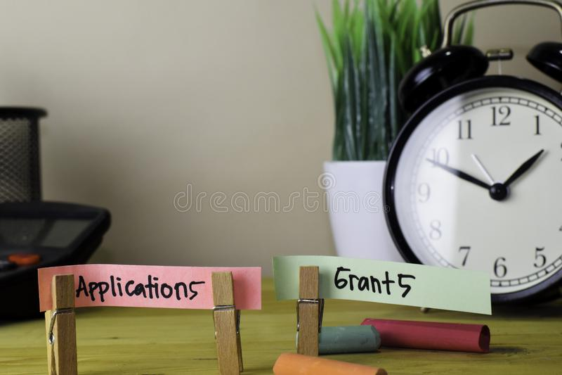 应用和津贴 在稠粘的笔记的手写在木办公桌上的服装扣子 库存照片