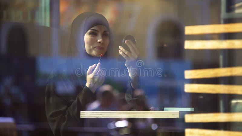 应用唇膏的可爱的自信回教夫人坐在咖啡馆,微笑 免版税库存照片