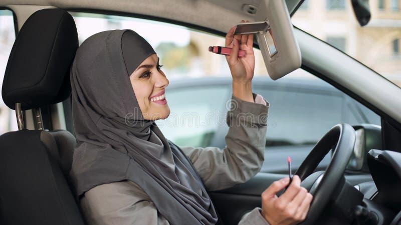 应用唇膏的可爱的自信回教夫人坐在汽车,蜂鸟 免版税库存图片