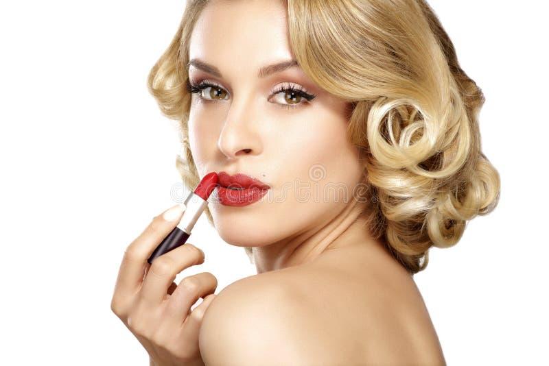 应用唇膏的美丽的年轻白肤金发的式样卷发 库存照片