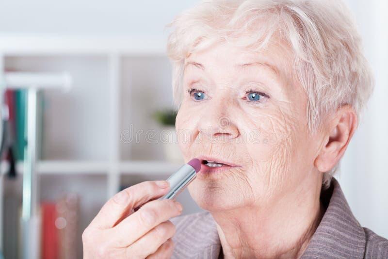 应用唇膏的资深妇女 免版税库存图片
