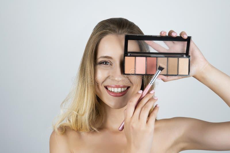 应用在刷子被隔绝的白色背景的美丽的年轻白肤金发的妇女藏品调色板眼影膏 免版税库存照片