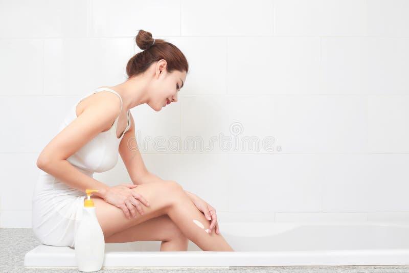 应用在她有吸引力的腿的年轻美丽的妇女身体化妆水 库存图片