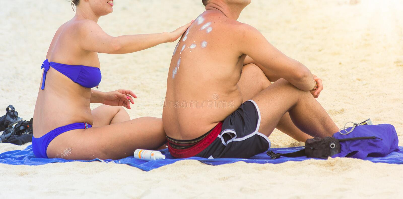 应用在她的丈夫后面的妻子遮光剂化妆水在海滩 库存照片
