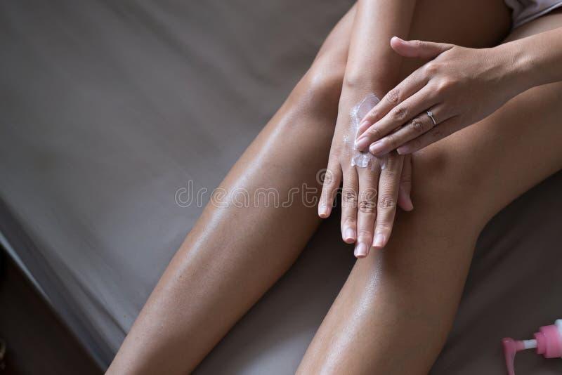 应用在她的手、概念健康和皮肤上的妇女润湿的奶油 库存照片
