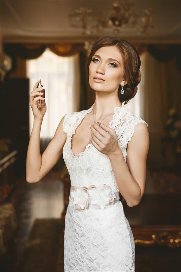 应用在她的脖子的年轻典雅和美丽的妇女香水 拿着瓶的时髦的鞋带礼服的时兴的深色的新娘 免版税库存照片