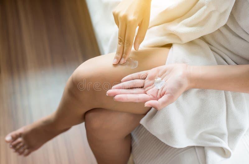 应用在她的腿、概念健康和皮肤的妇女润湿的奶油 免版税图库摄影