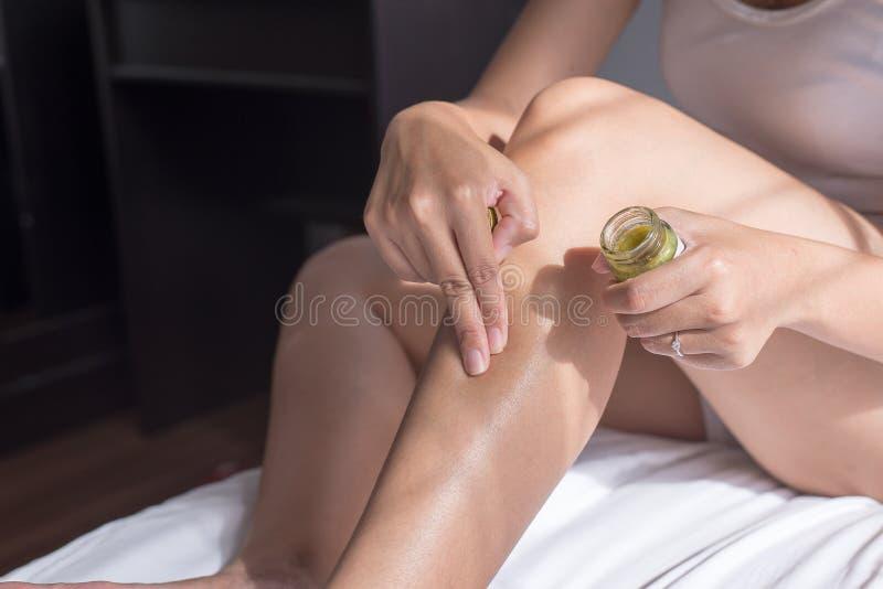 应用在她的腿从过敏,健康过敏护肤问题的妇女以疹和手奶油 免版税库存照片