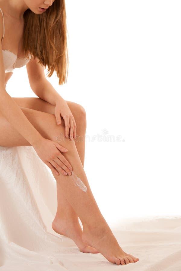 应用在她的腿的美丽的典雅的年轻女人润肤液是 库存图片