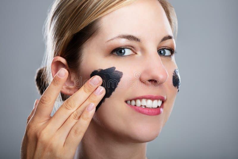 应用在她的面孔的妇女活性炭面具 免版税库存照片