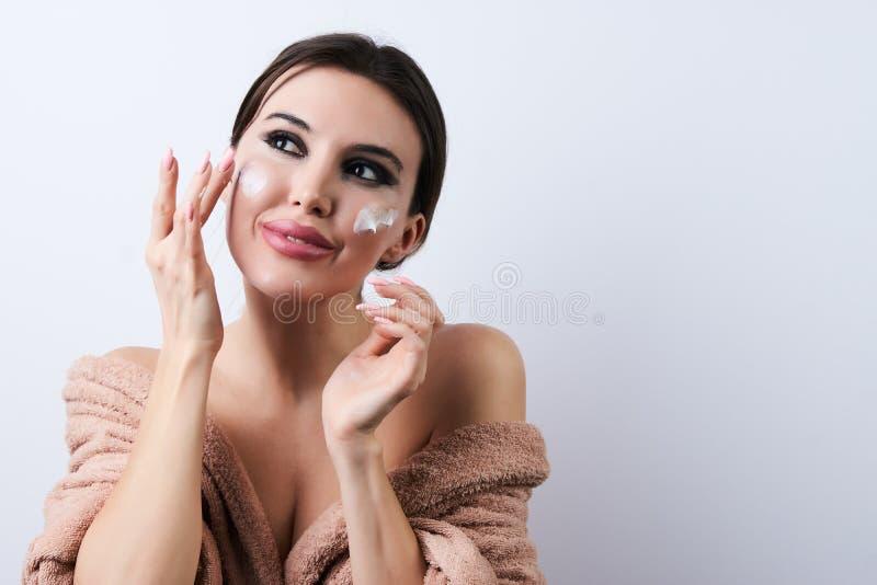 应用在她的面孔的年轻女人润肤霜,特写镜头 免版税库存图片