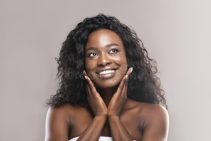 应用在她的面孔的年轻黑人妇女润肤霜奶油 免版税图库摄影