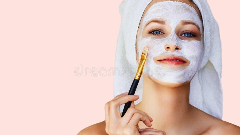 应用在她的面孔的美丽的年轻女人面膜与刷子 皮肤护理和治疗、温泉、自然美人和整容术 免版税图库摄影