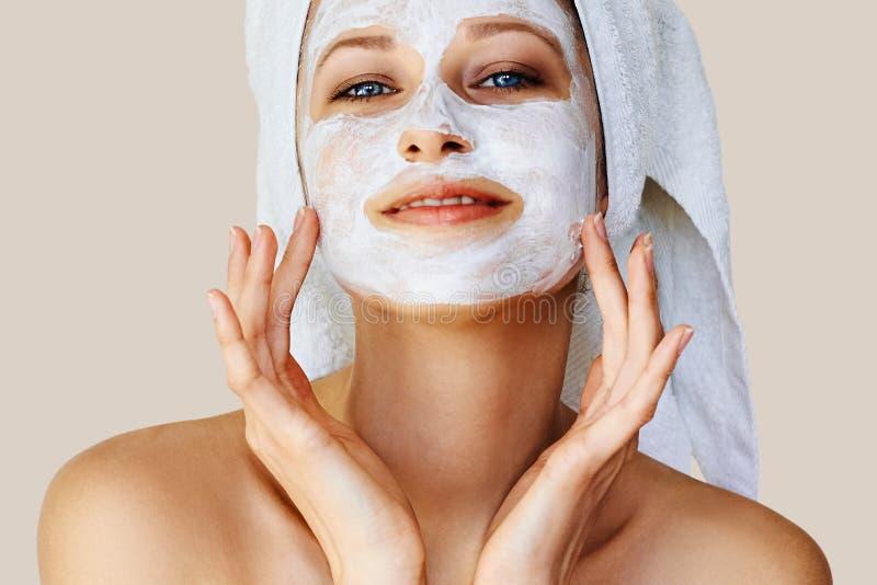 应用在她的面孔的美丽的年轻女人面膜 皮肤护理和治疗、温泉、自然美人和整容术概念 库存图片