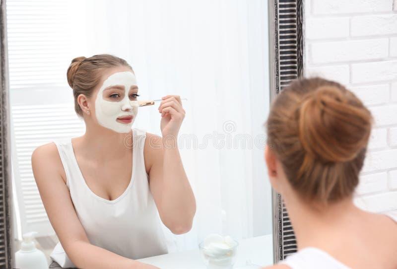 应用在她的面孔的美女自创黏土面具在镜子 库存照片