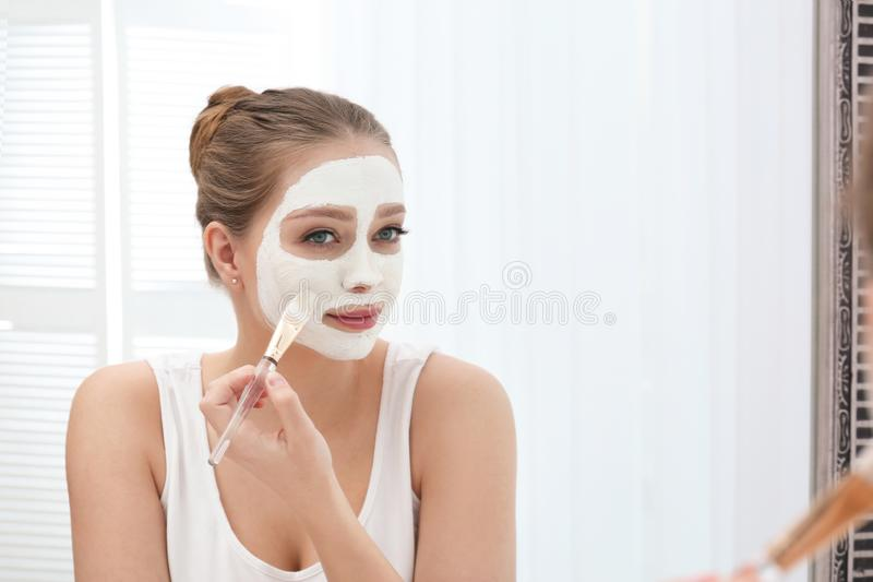 应用在她的面孔的美女自创黏土面具在镜子 免版税库存图片