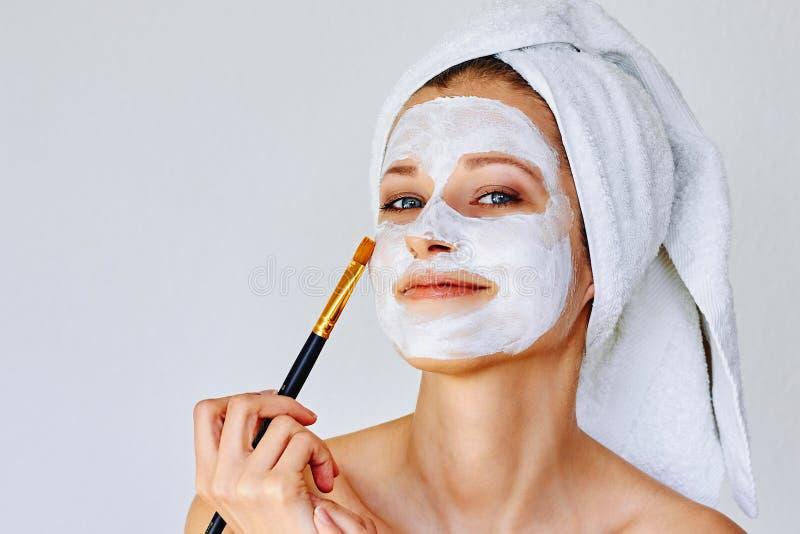 应用在她的面孔的美女面膜与刷子 o 库存照片
