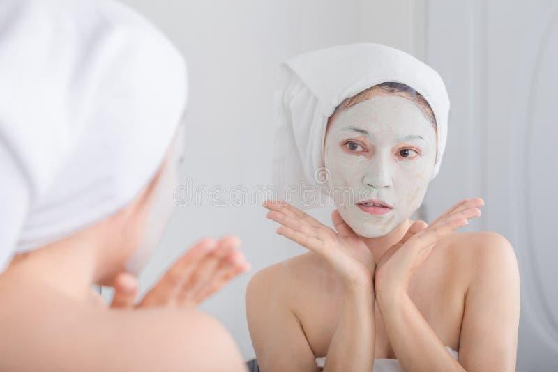 应用在她的面孔的面具和看在镜子的妇女 库存图片