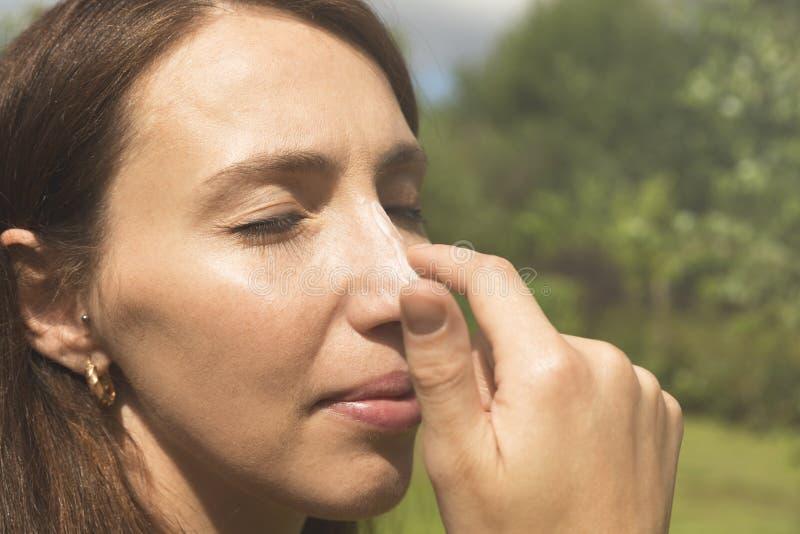 应用在她的鼻子的妇女遮光剂 Skincare 身体太阳保护 免版税库存照片