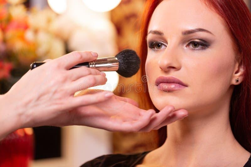 应用在妇女的面孔的化妆师液体音调的基础白色的腾出空位 r 免版税库存照片