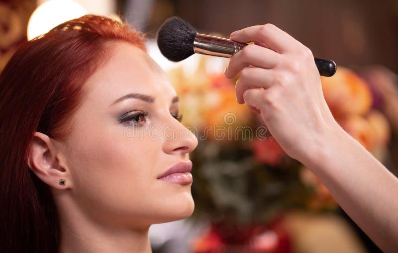 应用在妇女的面孔的化妆师液体音调的基础白色的腾出空位 r 免版税库存图片