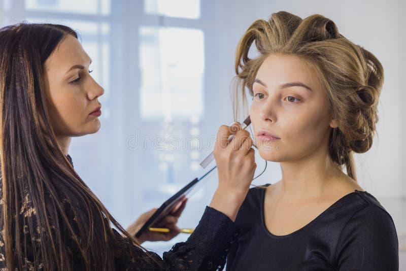 应用在妇女的面孔的化妆师液体音调的基础 库存图片