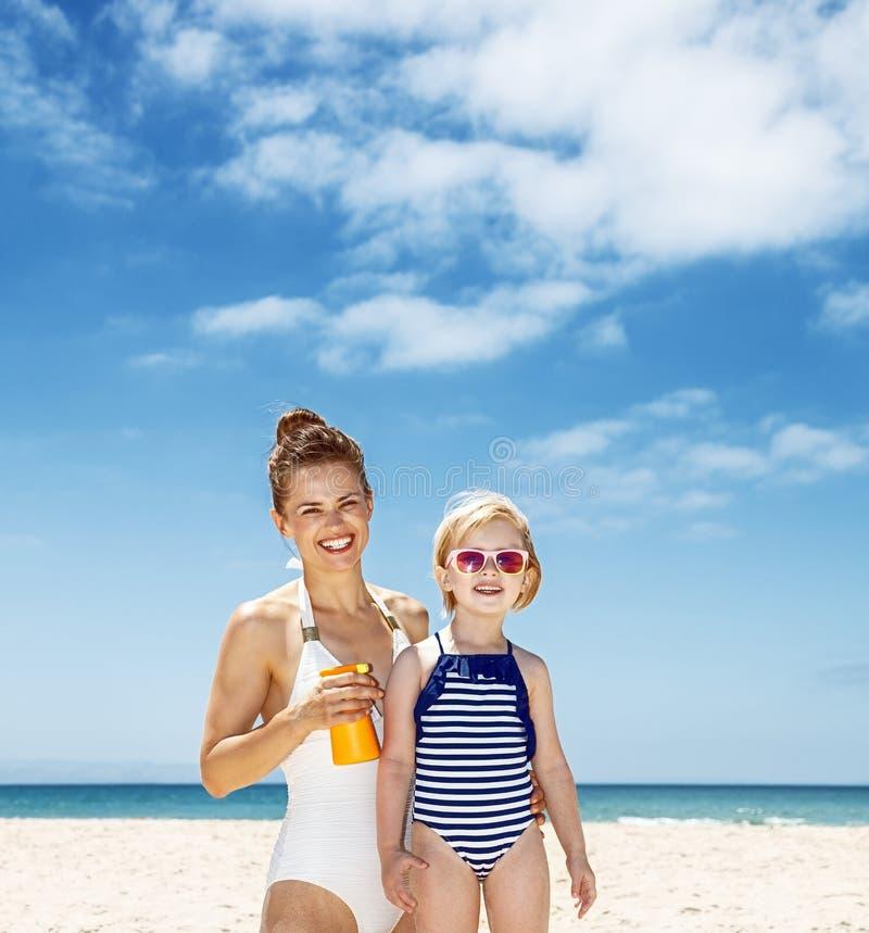 应用在孩子的愉快的母亲遮光剂泳装的在海滩 免版税图库摄影
