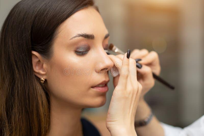 应用在模型的眼睛的明亮的基色眼影膏和拿着与眼影膏的化妆师壳在背景 免版税库存照片
