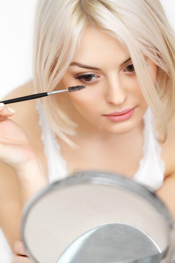 应用在睫毛的美丽的妇女染睫毛油。眼睛构成 免版税库存图片