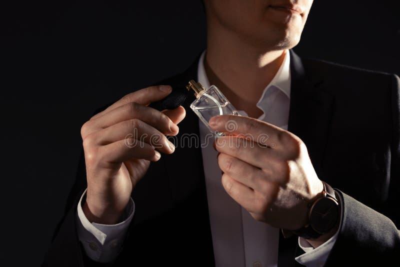 应用在脖子的帅哥香水反对黑背景 图库摄影