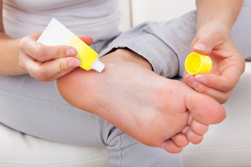 应用在脚的妇女奶油 免版税库存照片