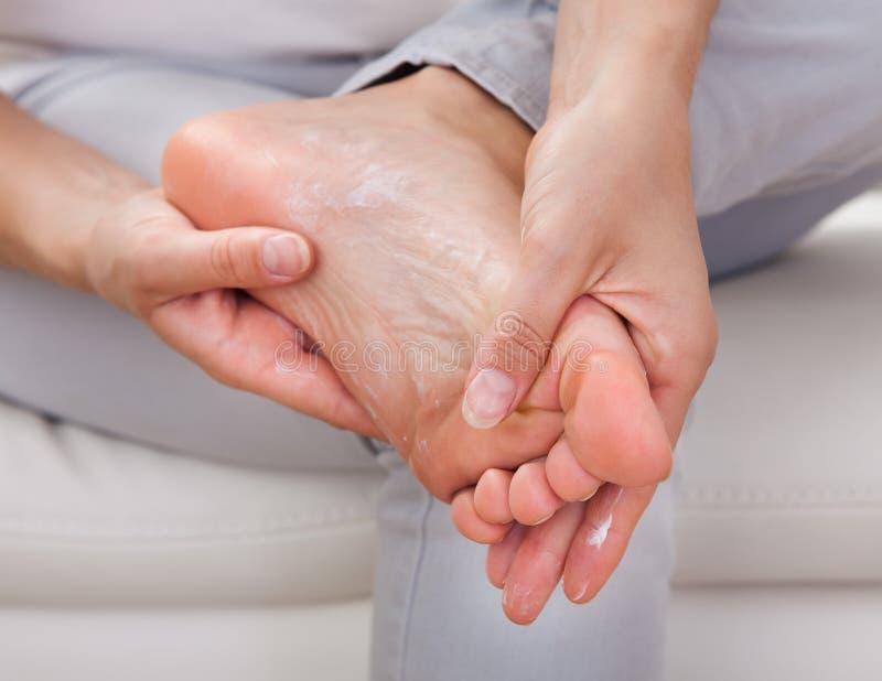 应用在脚的妇女奶油 免版税库存图片