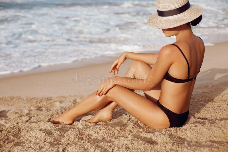 应用在腿的秀丽妇女防晒霜化妆水 润肤液 在美好的腿的一种女性污迹遮光剂在海滩 免版税库存图片