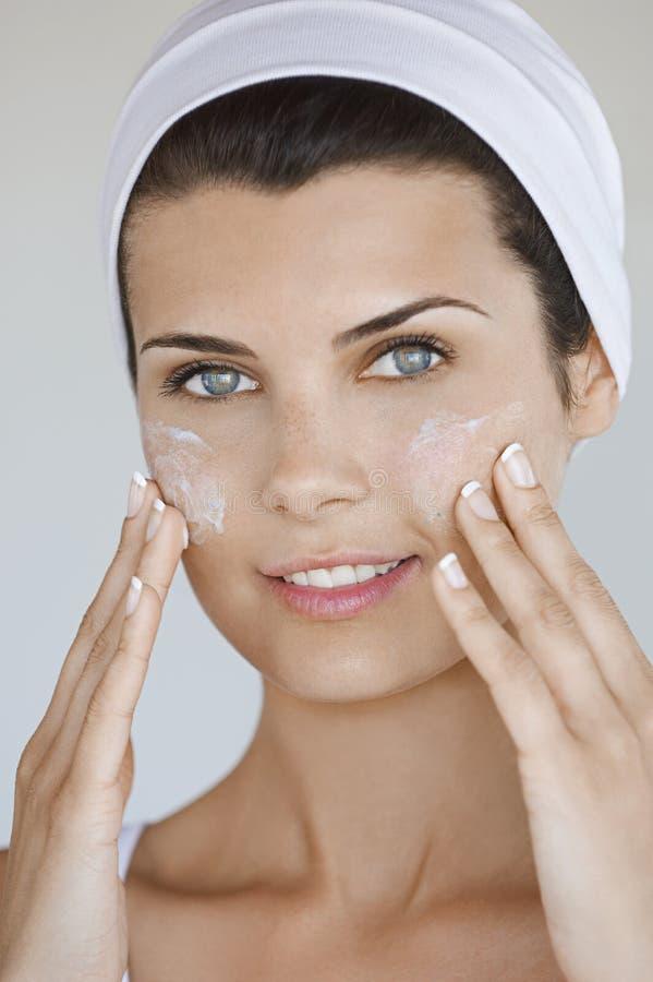 应用在面孔的妇女奶油 图库摄影
