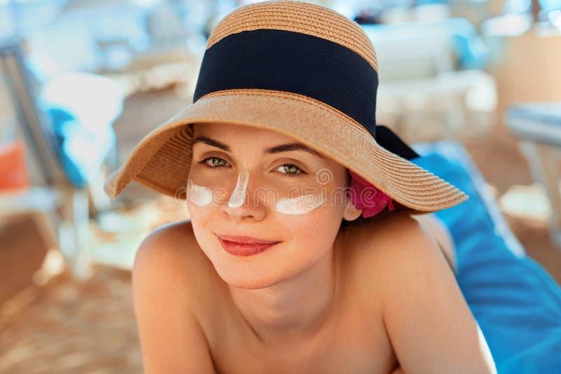 应用在面孔的妇女微笑防晒霜 Skincare 身体太阳保护 遮光剂 库存照片