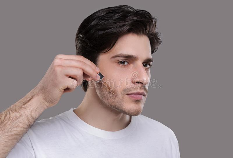 应用在面孔的帅哥润湿的血清 免版税库存图片
