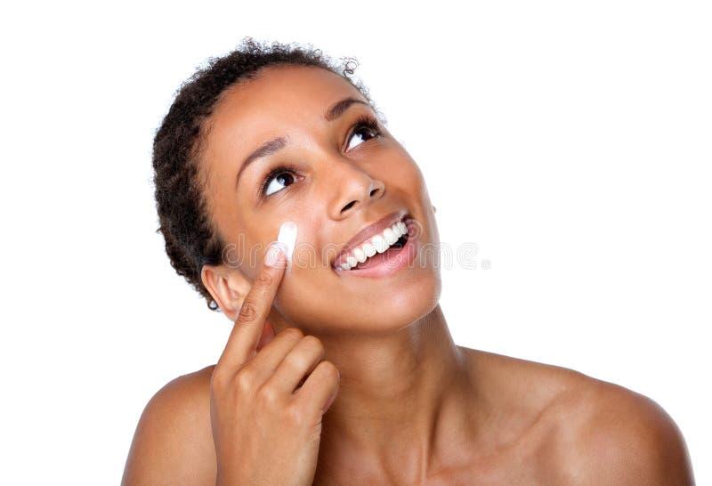 应用在面孔的微笑的妇女化妆水 免版税库存照片