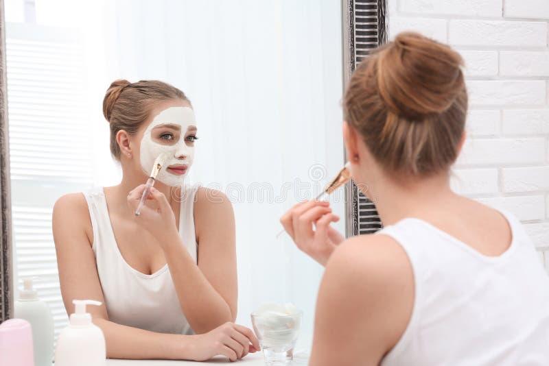 应用在面孔的美女自创黏土面具在镜子户内 图库摄影