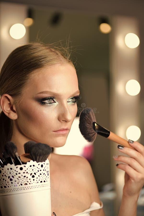 应用基础粉末的美丽的少妇或脸红与构成刷子 库存图片