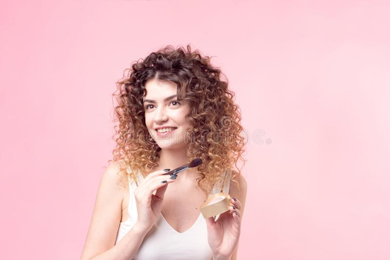 应用基础粉末的美丽的年轻女人或脸红与构成刷子 免版税库存照片