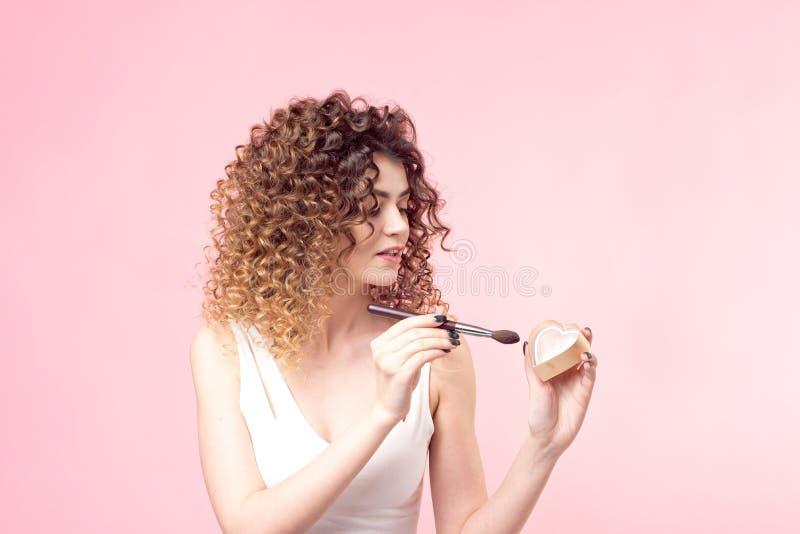 应用基础粉末的美丽的年轻女人或脸红与构成刷子 免版税库存图片