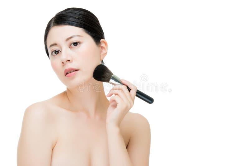应用基础粉末的迷人的少妇脸红与makeu 免版税图库摄影