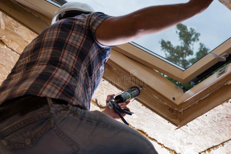 应用堵头的建筑工人于天窗 免版税库存图片