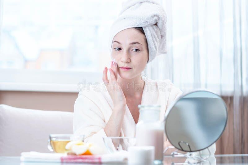 应用天然化妆品的奶油在润湿皮肤的面孔的美丽的年轻女人 卫生学和喜欢皮肤 库存图片