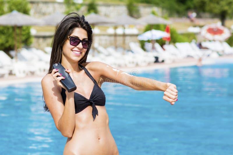应用太阳保护奶油的美丽的微笑的妇女 库存图片